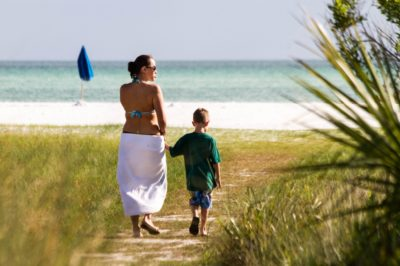 MustDo.com | Mother and son walk to white sand beach Siesta Beach Sarasota, Florida