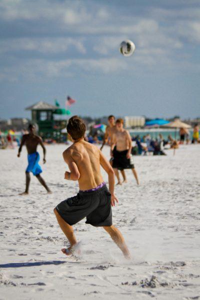 MustDo.com | Kids play soccer, near beach volleyball on Siesta Beach Sarasota, Florida