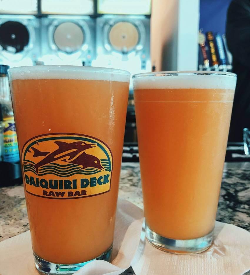 "Daiquiri Deck Raw Bar restaurant's ""Deck Sauce"" original Daiquiri Deck/Big Top Brewing Hazy Guava IPA beer. Must Do Visitor Guides | MustDo.com"