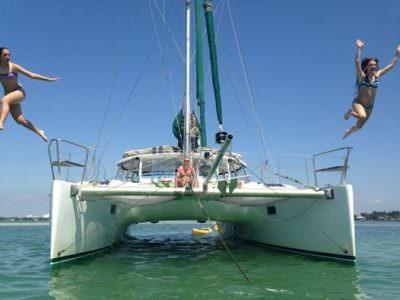MustDo.com | Girls Jumping from bow of Kathleen D Sailing Catamaran Longboat Key, Florida