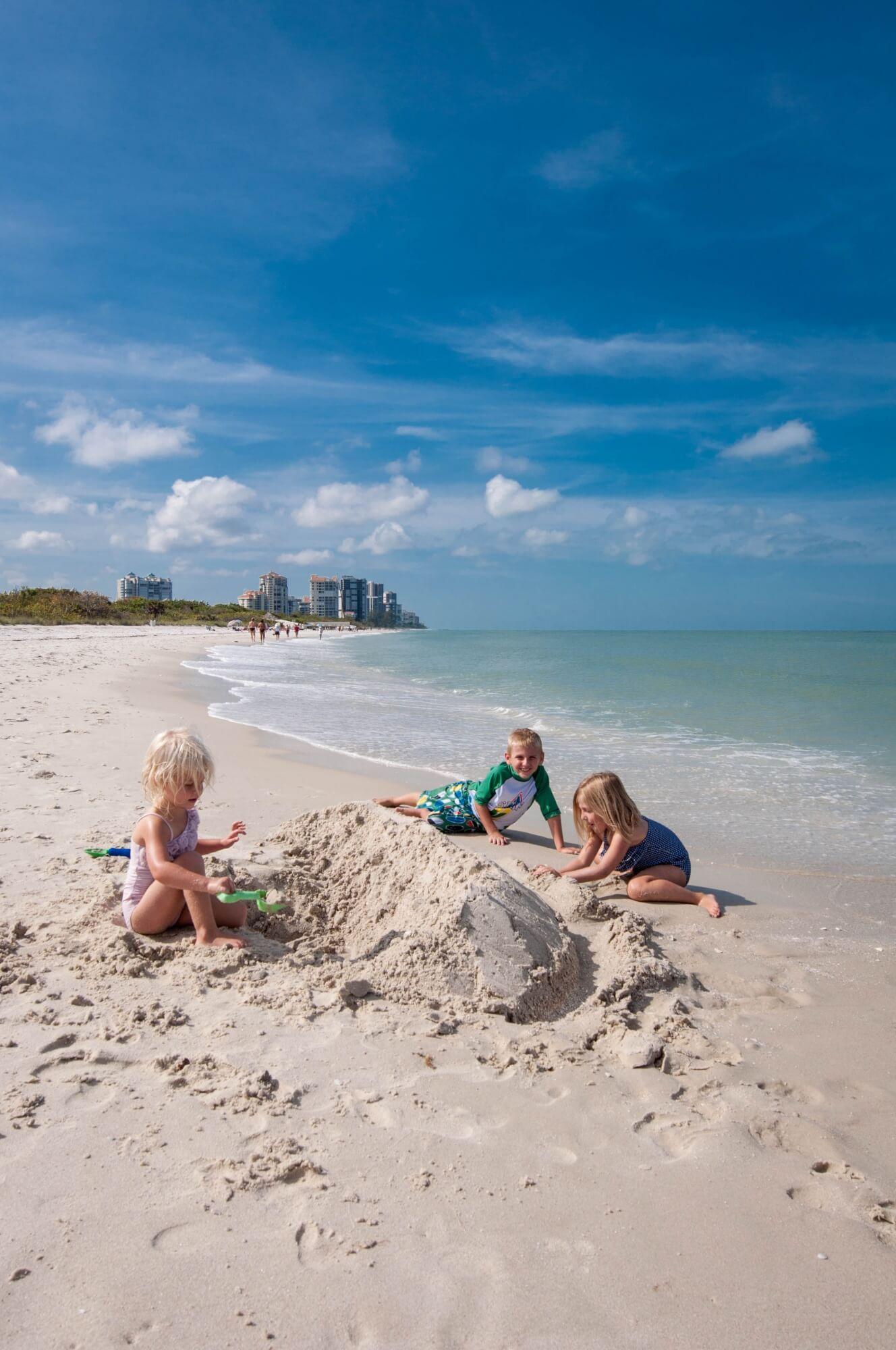 MustDo.com | Kids build a sandcastle in the white sand beach at Clam Pass Beach Naples Florida. Photo by Debi Pittman Wilkey.