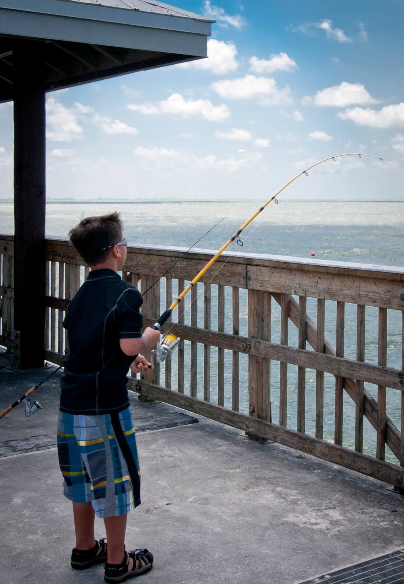 Boy fishing off the Fort Myers Beach Pier Fort Myers, Florida.