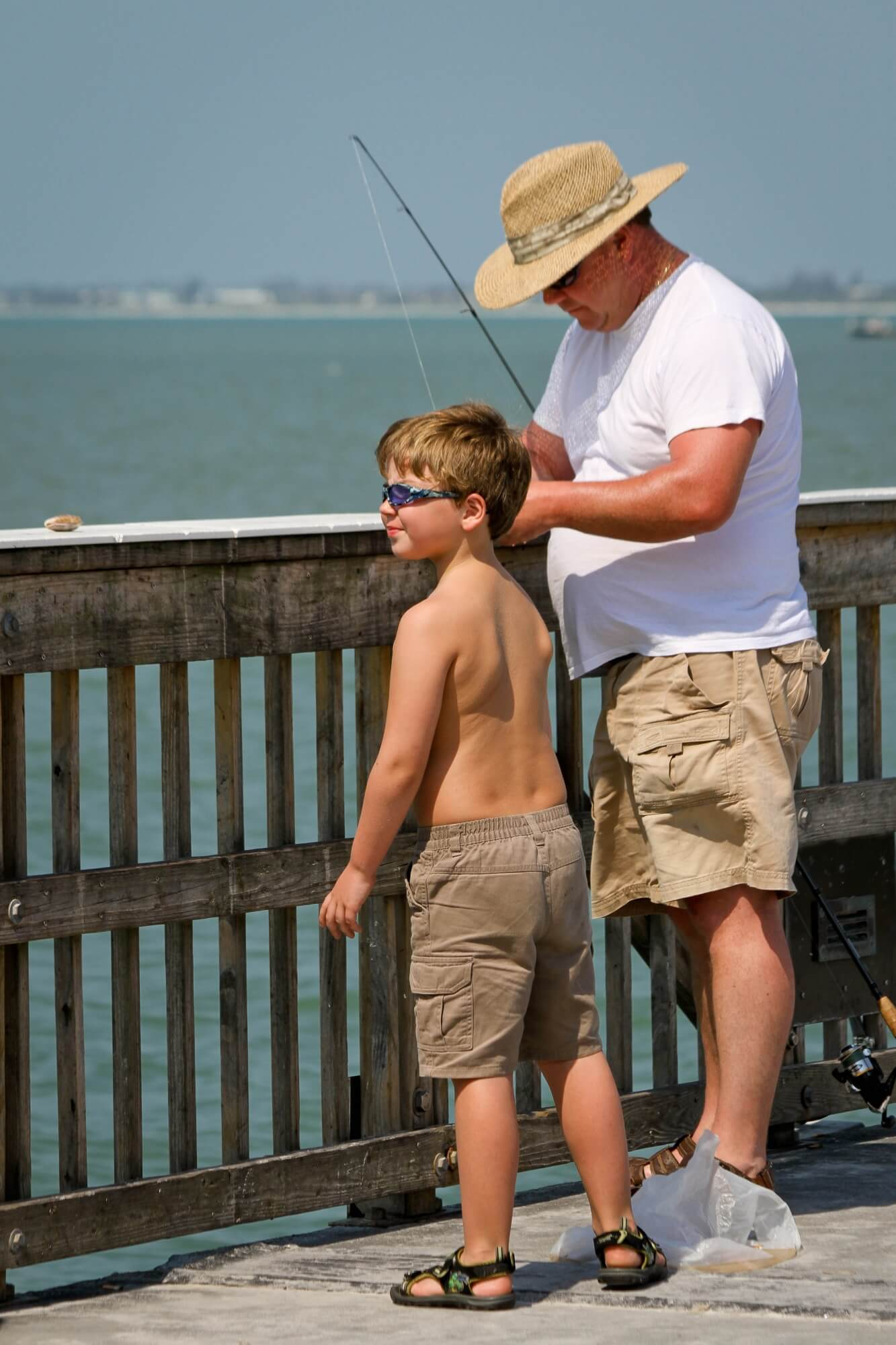 Young boy fishes from the pier with dad Southwest Florida.