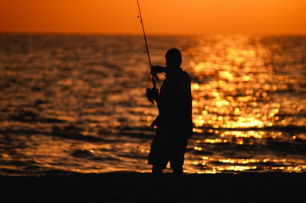 Fisherman casts a line from the beach at sunset in Southwest Florida.