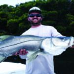 Fisherman shows off his snook catch Southwest Florida. Photo by Elizabeth Lempriere for Must Do Visitor Guides.
