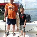 Young boy shows off his fresh catch caught on Wolfmouth Charters fishing trip Sarasota, FL
