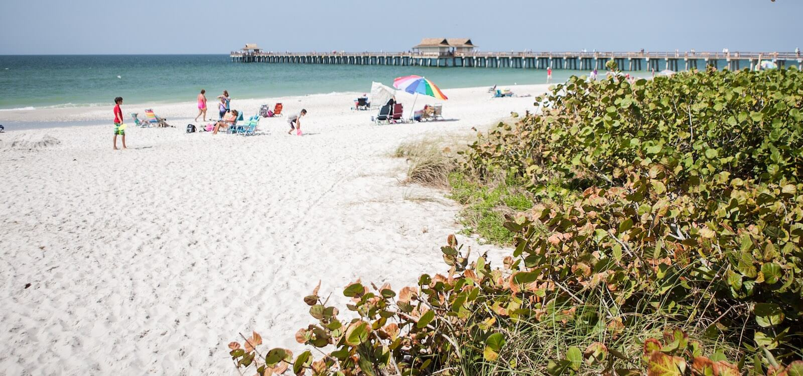 MustDo.com | White sand beach and the Naples Beach Pier Naples, Florida. Photo by Mary Carol Fitzgerald.