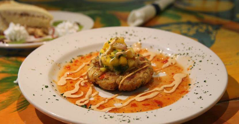 Blue Giraffe restaurant's Giraffe Cake pan seared crab cake topped with mango salsa, chipotle cream and sweet chili glaze. Sanibel, Florida. Must Do Visitor Guides Florida vacation information. MustDo.com