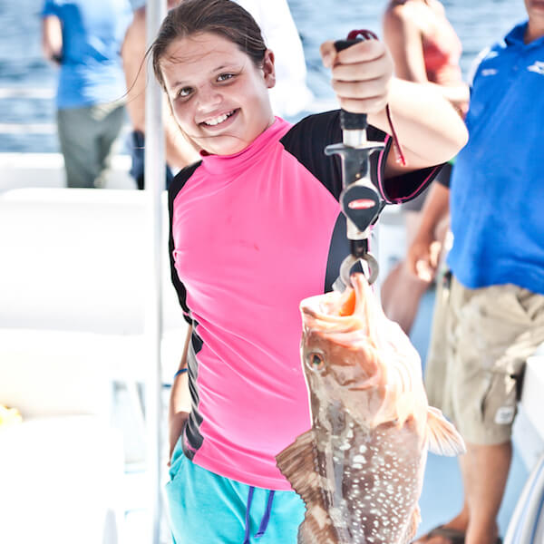 MustDo.com | Showing off her catch. Pure Florida offers private and shared offshore deep sea, calm bay, and near coastal fishing charters for beginners to seasoned anglers of all ages. Photo by Mary Carol Fitzgerald.