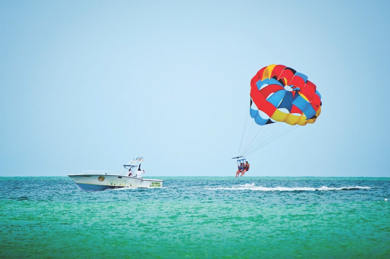 Soar high above the Gulf of Mexico on an exhilarating parasailing ride in Fort Myers, Florida. Must Do Visitor Guides, MustDo.com
