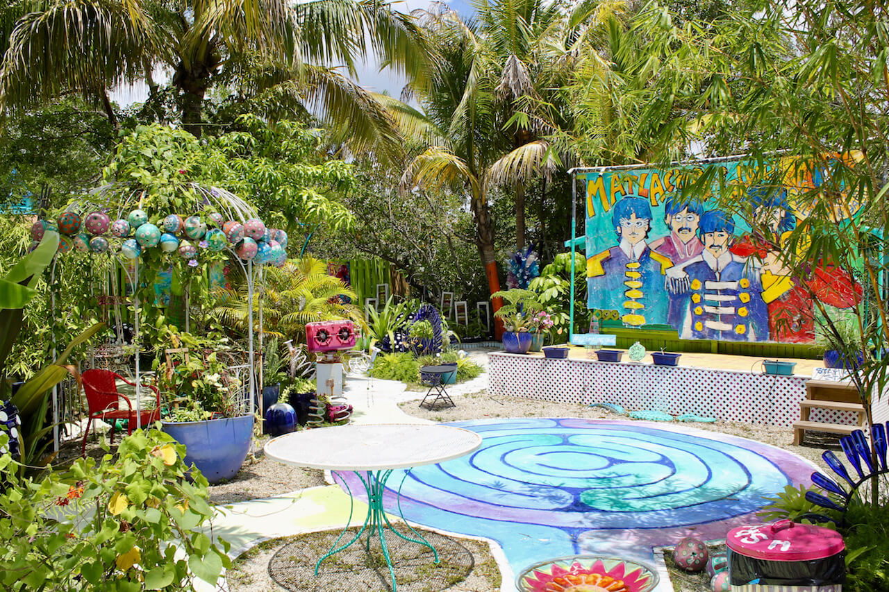 The bright colors of Leona Lovegrove's paintings are carried outside to the whimsical garden behind the gallery in Matlacha, Florida. | Must Do Visitor Guides
