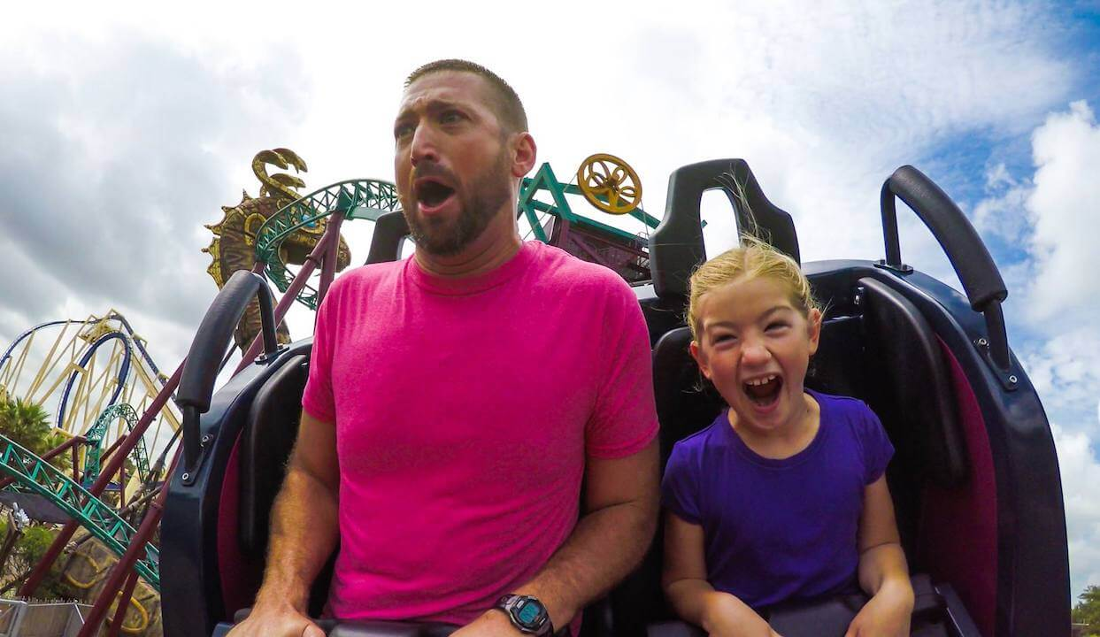 Man with child looking excited on Cobras Curse roller coast ride Busch Gardens Tampa Bay. Must Do Visitor Guides, MustDo.com