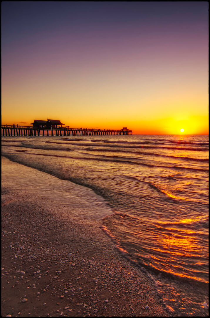 Watch the sun set over the historic Naples Pier in Naples, Florida. Photo by Jennifer Brinkman. Must Do Visitor Guides, MustDo.com.