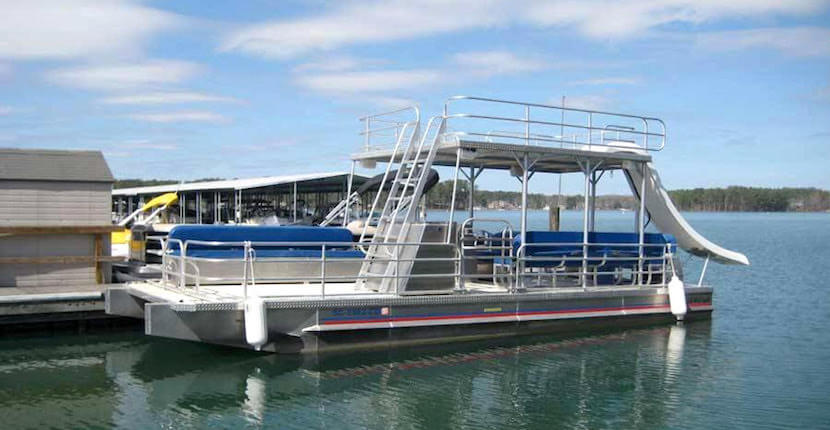 Pontoon with slide at the dock of Fort Myers Beach Sea & Sun. Explore the waters of Fort Myers Beach with half-day, daily, or weekly pontoon, deck, or center console boat rental. Must Do Visitor Guides, MustDo.com