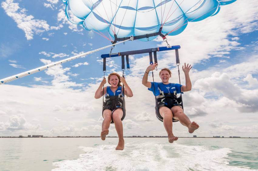 Two girls smiling on an exciting parasail ride over the water.