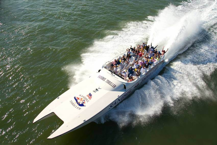 Sanibel Thriller boat tour speeds across the water with a boat full of excited passengers.