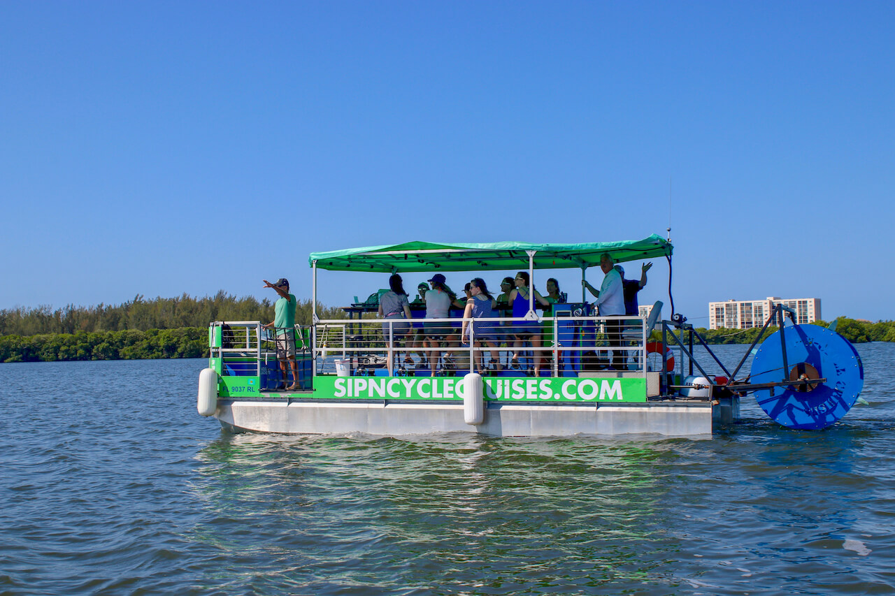 Pedal at your own pace while your captain navigates on a fun pedal power water cruise that includes a stop at a bar/restaurant. Sip-N-Cycle Cruises pedal boat tours Siesta Key, Florida.  Boat accommodates up to 16 guests–ten at pedal stations surrounding a central bar, and six others on bench seating. The boat's two coolers are fully stocked with ice to keep your drinks cold. Guest can bring up to 36 oz. of beer (cans only please) or 18 oz. of wine! Photo by Nita Ettinger. Must Do Visitor Guides | MustDo.com