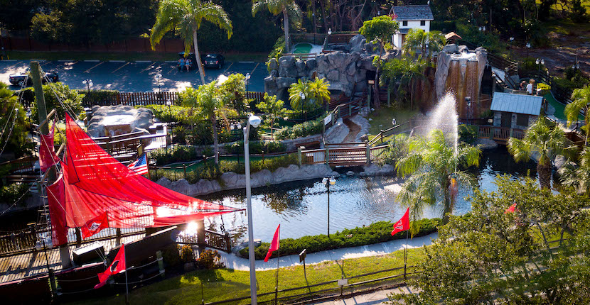 Play 18 holes of challenging mini-golf in a lush tropical setting amid waterfalls, caves, pirate ships, and live alligator at Smuggler's Cove in Sarasota, Florida.
