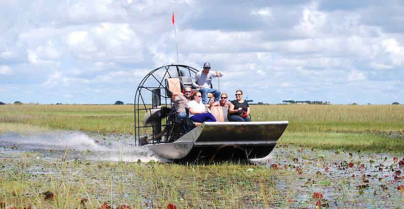Everglades Swamp Tours airboat with passengers glides across the water.