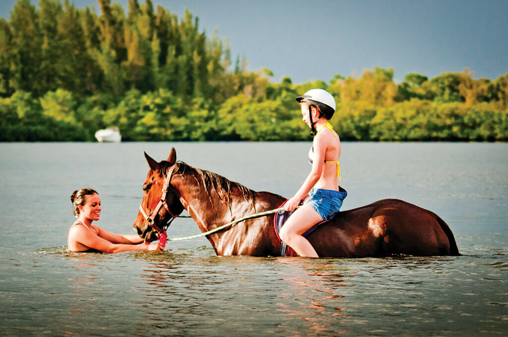 Young teen wearing helmet on horse swim in Palma Sola Bay, Bradenton, Florida, USA.