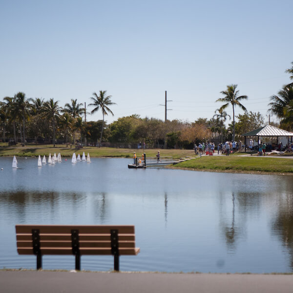 Mackle Park on Marco Island, Florida features paved walkways along the edge of a small lake, community center, dog park, covered basketball court, volleyball court, soccer field, children's playground and splash park.