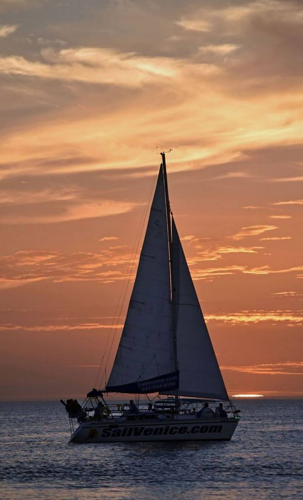 Sunset on the Gulf of Mexico with Sail Venice sailboat in the foreground.