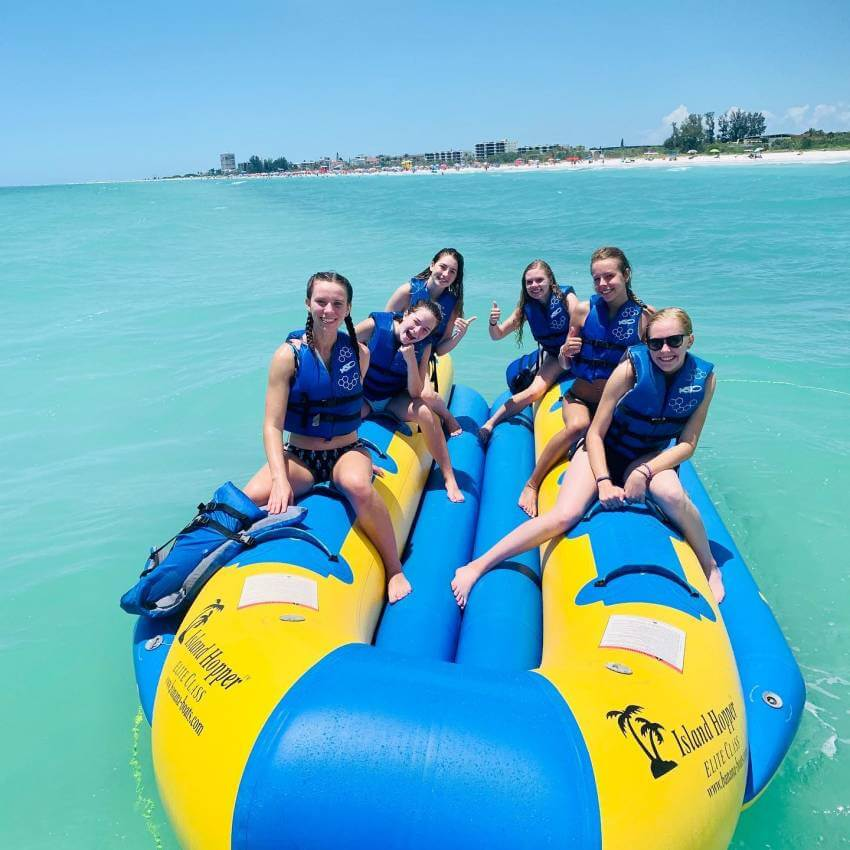 Six girls smiling on a banana boat raft on the water near the beach on Siesta Key, Florida.