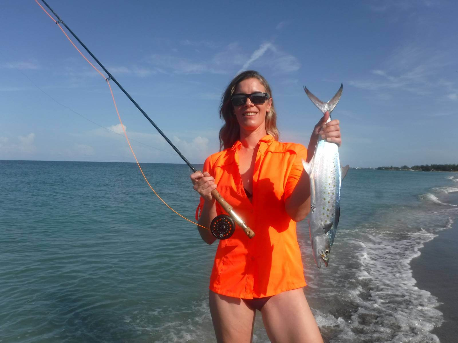 Woman holding up a spanish mackerel fish caught fishing at the beach Sarasota, Florida.