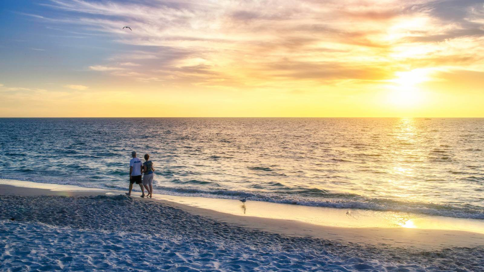 Couple on a romantic walk on the beach with the sun setting over the Gulf of Mexico Naples, Florida.