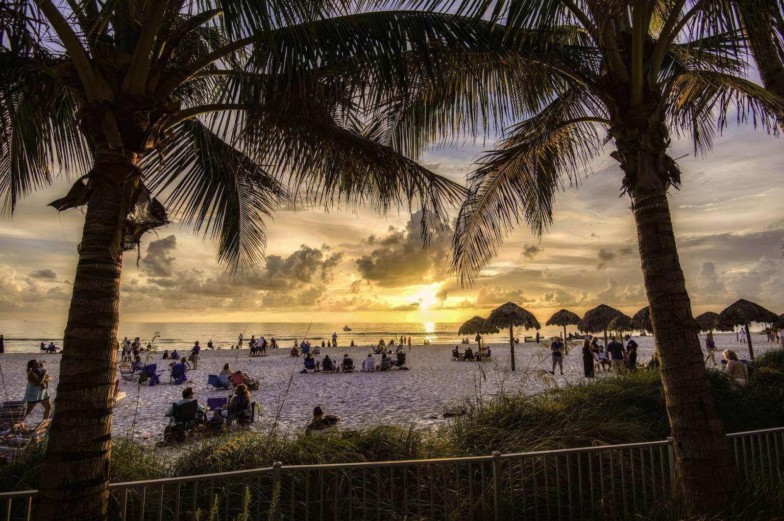 Beach visitors enjoy Clam Pass Beach Park at sunset in Naples, Florida.