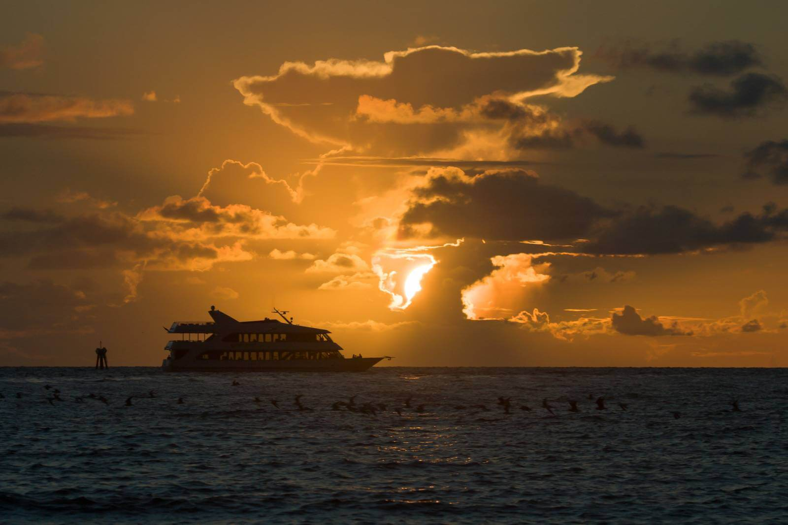 Luxury yacht on the horizon with spectacular sunset Gulf of Mexico Naples and Marco Island, Florida.