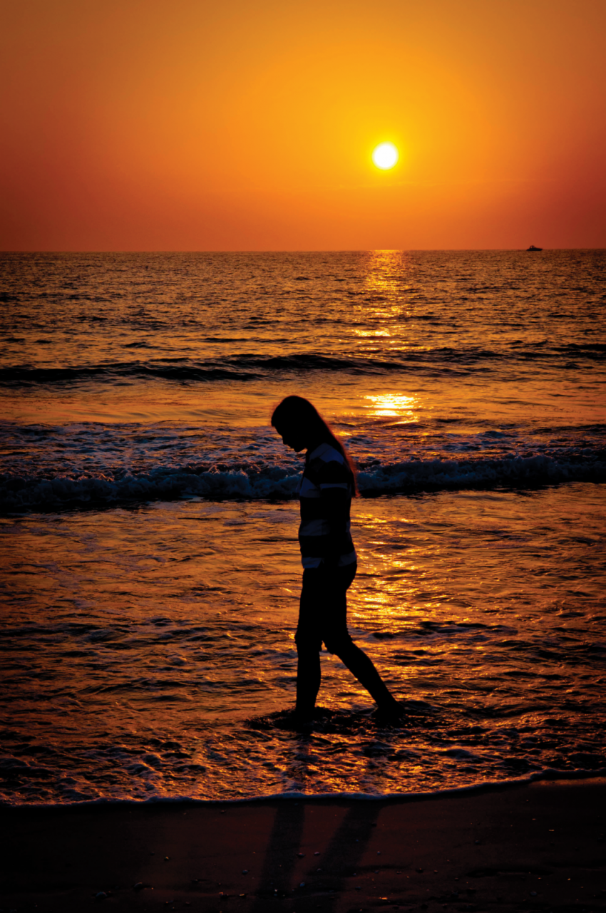 Young girl walks along the waters edge at the beach with the sunset on the Gulf of Mexico Marco Island, Florida.
