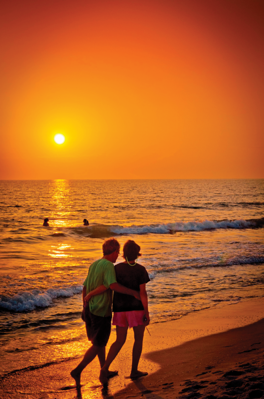 Couple walks along the beach with a gold and orange Gulf of Mexico sunset in Naples, Florida.