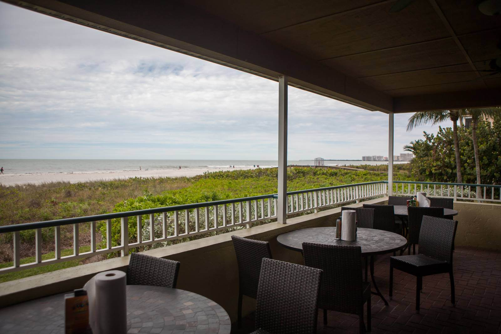 Tables overlooking the beach and Gulf of Mexico at the Sunset Grille restaurant Marco Island, Florida.