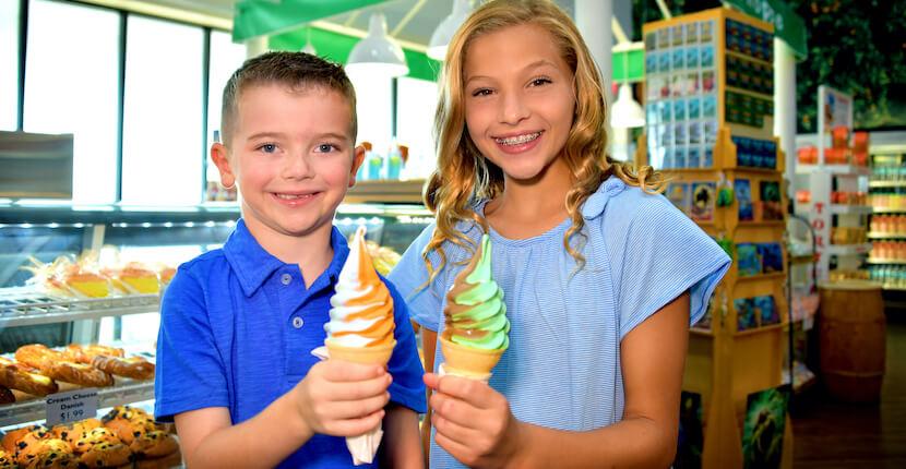 Happy kids holding soft serve swirl ice cream cones at Sun Harvest Citrus in Fort Myers, Florida.