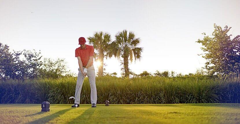 Man teeing off on golf course in Ave Maria, Florida.