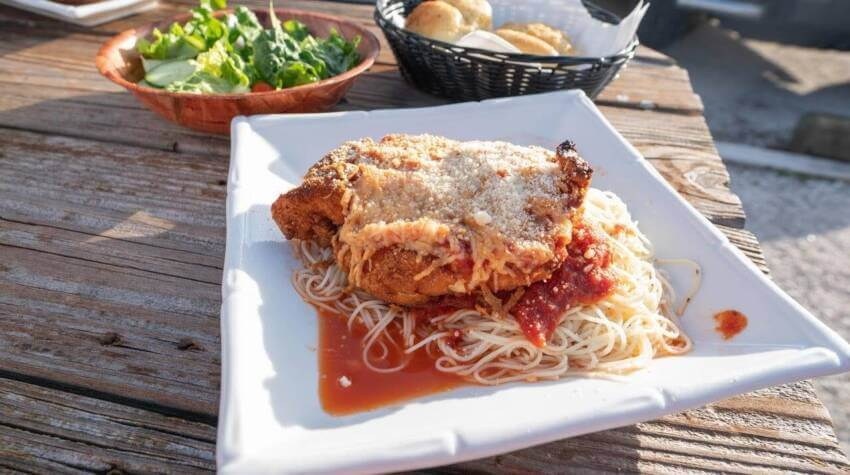 Chicken Parmesan on a bed of pasta with side salad and bread. Crabby Lady restaurant Goodland, Florida.