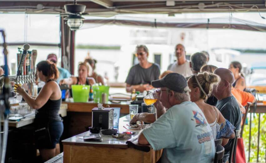 Men and women enjoying food and drink at the Crabby Lady restaurant and bar in Goodland, Florida.