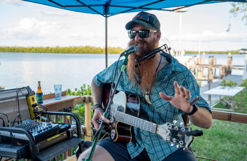Man with guitar playing live music at Crabby Lady waterfront restaurant Goodland, Florida.