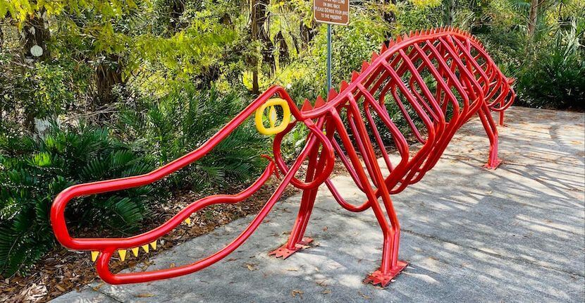 Red metal alligator sculpture on pavement trail Six Mile Cypress Slough Preserve Fort Myers, Florida.