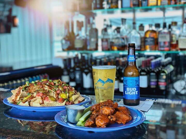 Marina Jack waterfront bar in Sarasota with a plate of buffalo chicken wings, plate of loaded nachos, bottle of Bud Light and glass of beer on bar counter