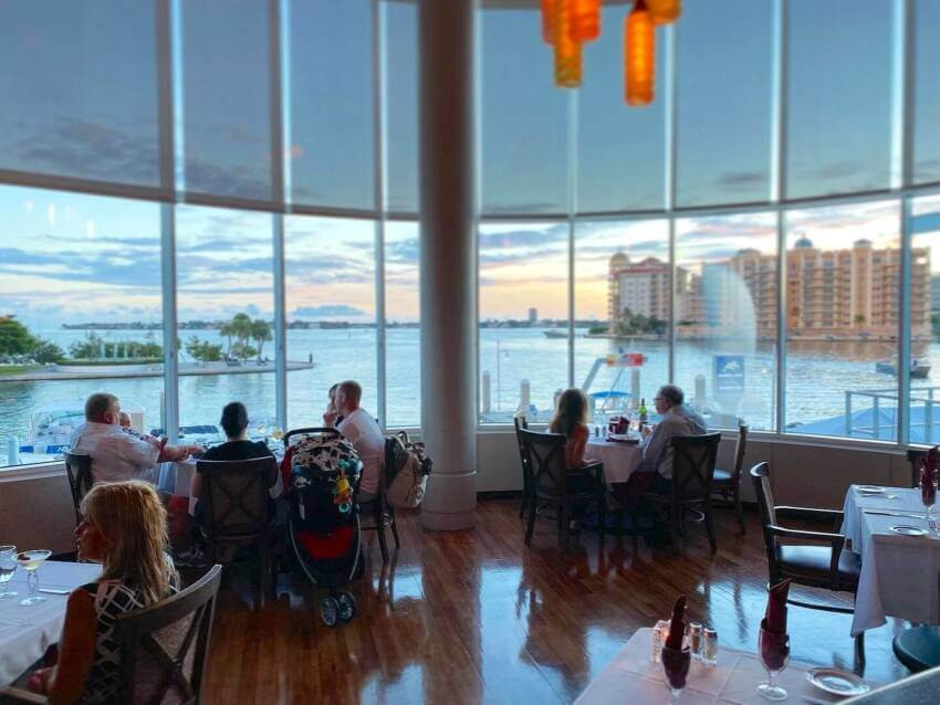 People dining at Marina Jack waterfront restaurant overlooking the water and sunset in Sarasota, Florida