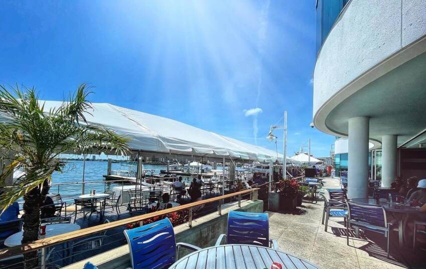Blue sky and sunshine with outdoor dining tables at waterfront restaurant Marina Jack in Sarasota, Florida.